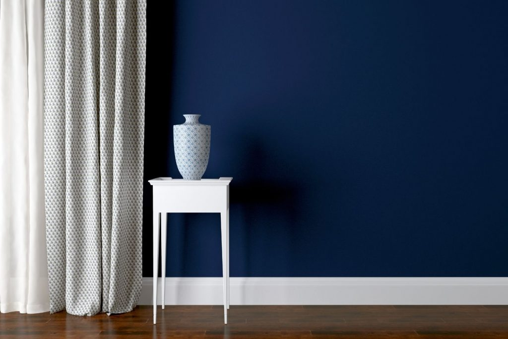 navy painted wall with white baseboards - a great color for a dark hallway