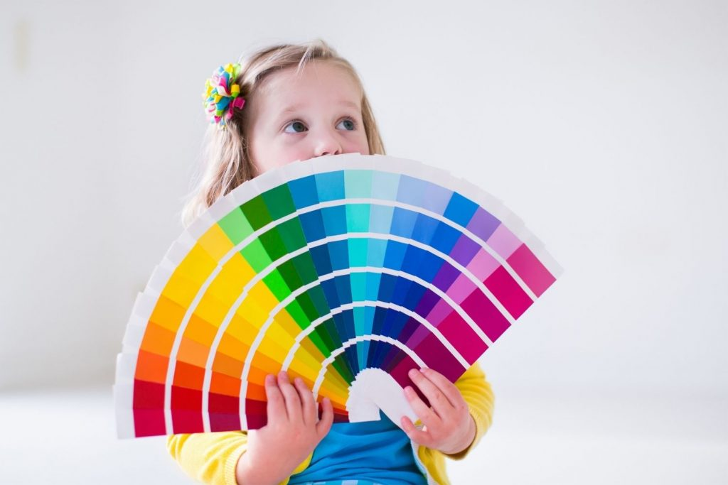 little girl holding a fandeck, wondering how to choose a color palette