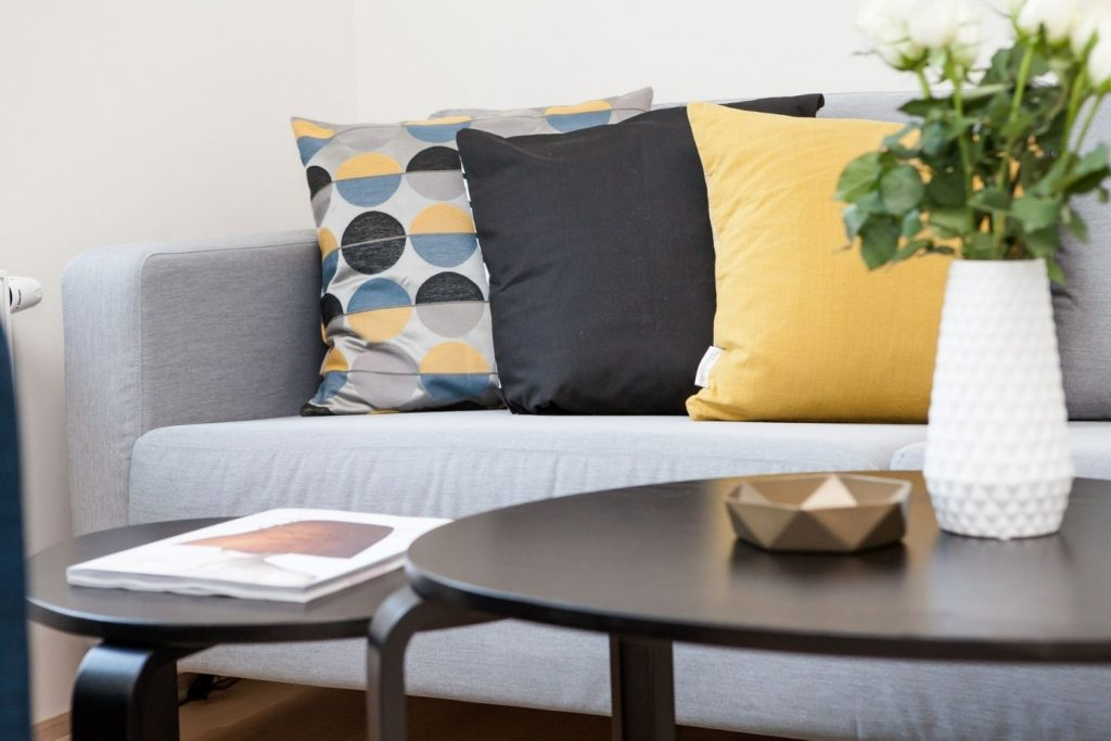 neutral sofa with gray and yellow accent pillows