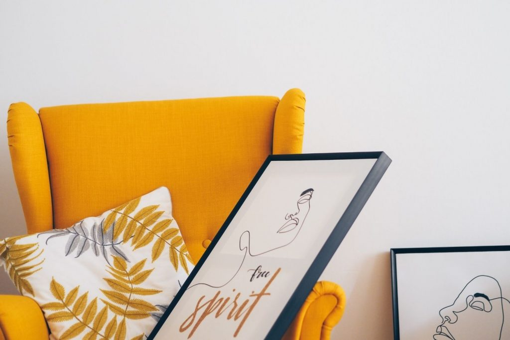orange chair with accent pillow and artwork