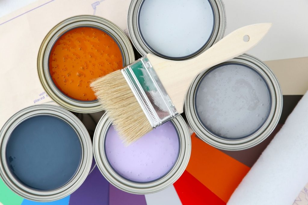 paint brush on top of paint cans - fratured photo for the article on Whole House Color Palette by sherwin williams
