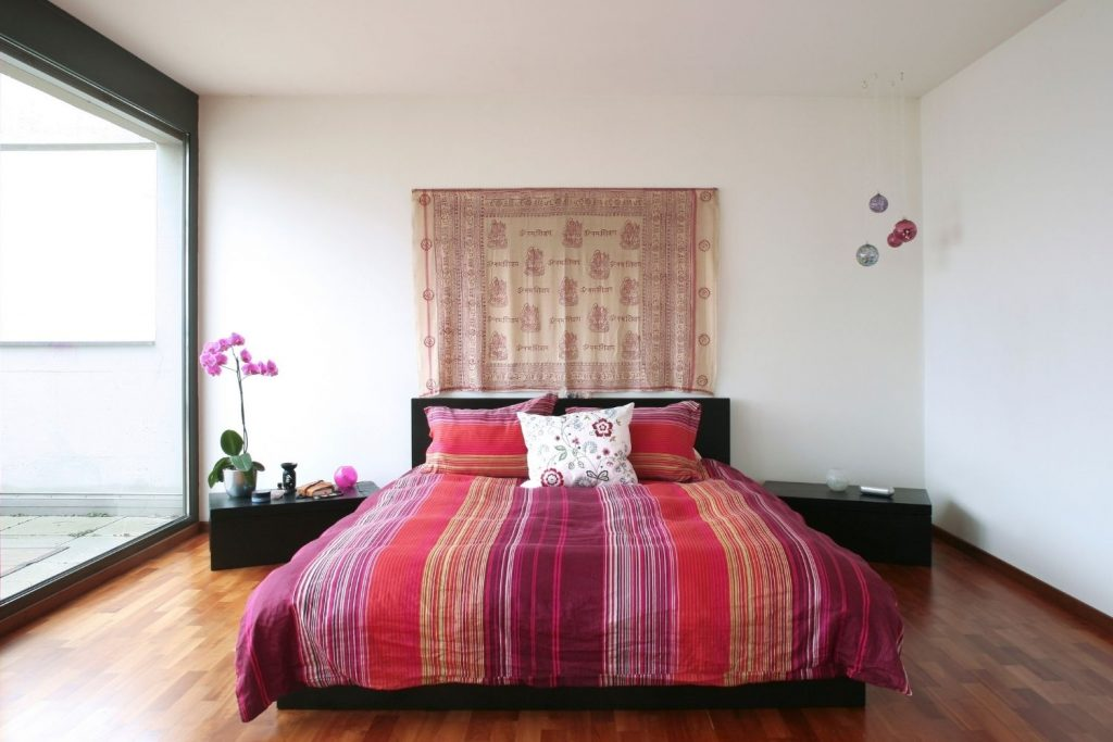 bedroom with a tapestry hanging above the bed