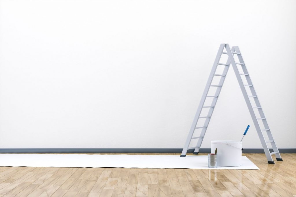 room with white painted walls, a ladder, and paint can