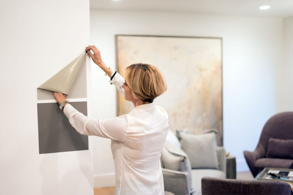 woman hanging peel and stick samples on the wall