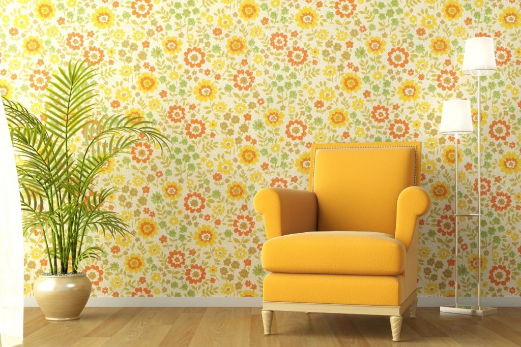 featured image of a wallpapered wall & yellow armchair for the article onhow to choose wallpaper for small living room