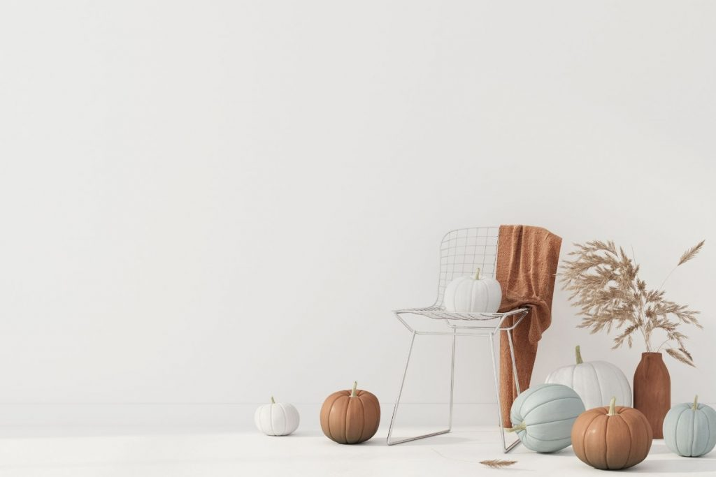 painted pumpkins and a chair draped with a blanket