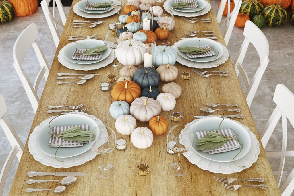 featured image for article on thanksgiving colors and what they mean -- a table set with white and blue dishes and multi-colored pumpkins as a centerpiece