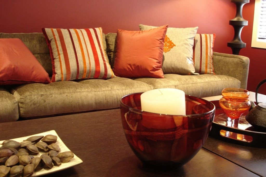 gold sofa with orange and gold pillows