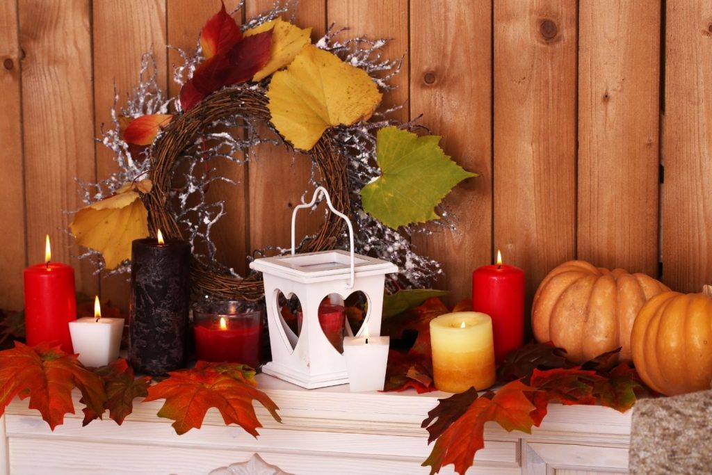 fireplace mantel decorated with a fall wreath, candles, and pumpkins in red, orange, yellow, and gree